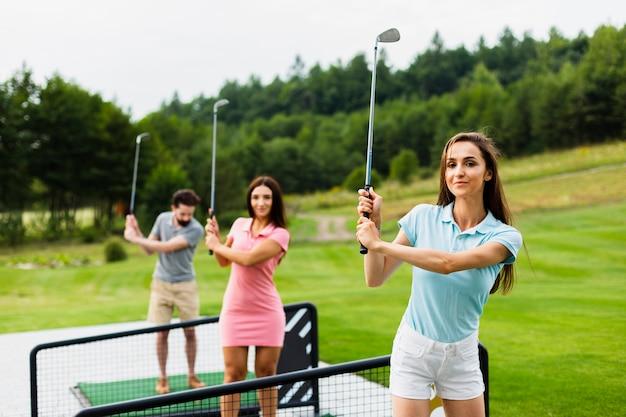 Vooraanzicht van jonge golfers met stok omhoog