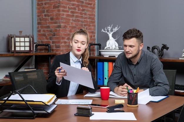 Vooraanzicht van jonge hardwerkende bedienden die één probleem bespreken in de documenten op kantoor
