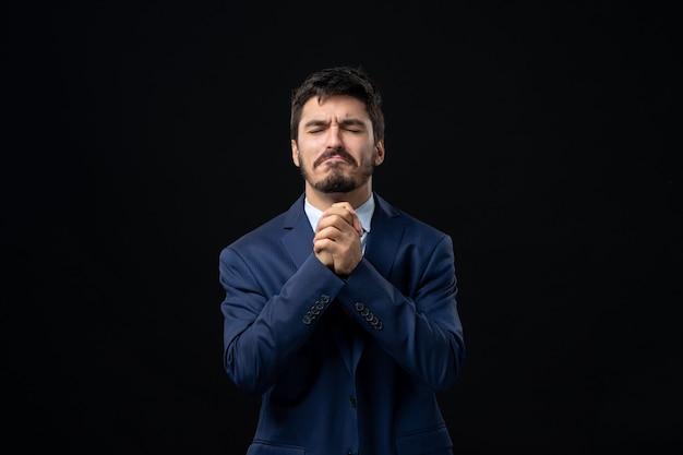 Vooraanzicht van jonge hoopvolle bebaarde man die bidt voor god op geïsoleerde donkere muur