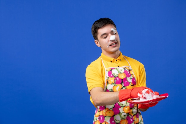 Vooraanzicht van jonge huishoudster met schuim op zijn gezicht die plaat op blauwe muur wast
