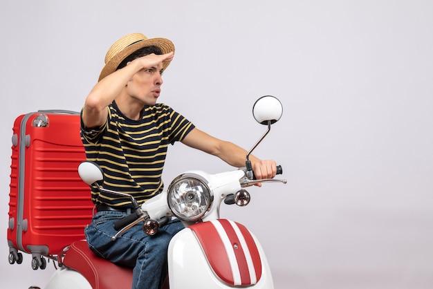 Vooraanzicht van jonge jongen met strohoed rijden bromfiets