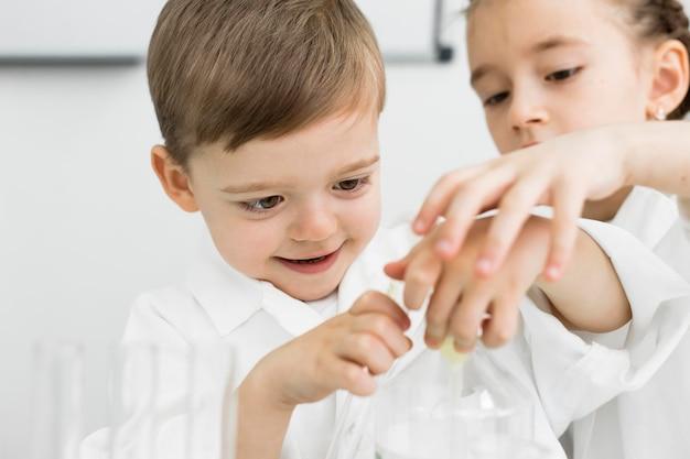 Vooraanzicht van jonge kinderen wetenschappers met reageerbuizen