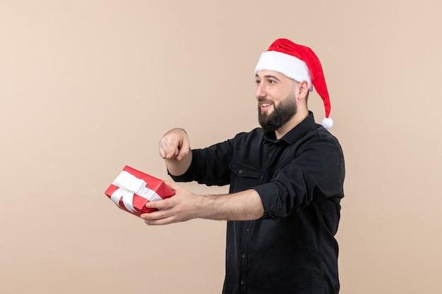 Vooraanzicht van jonge man die cadeau geeft aan iemand op de roze muur