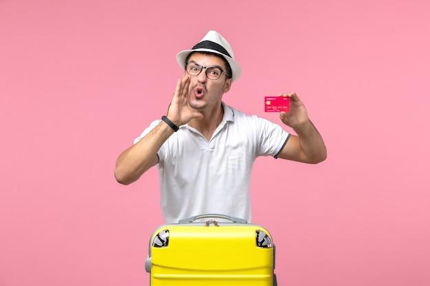 Vooraanzicht van jonge man die emotioneel bankkaart vasthoudt op vakantie op roze muur