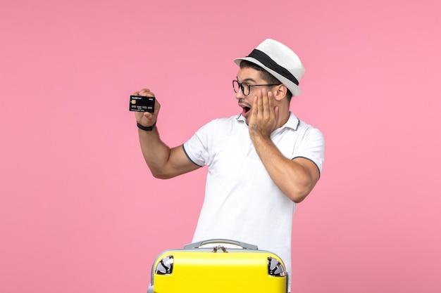 Vooraanzicht van jonge man die emotioneel zwarte bankkaart op de roze muur houdt