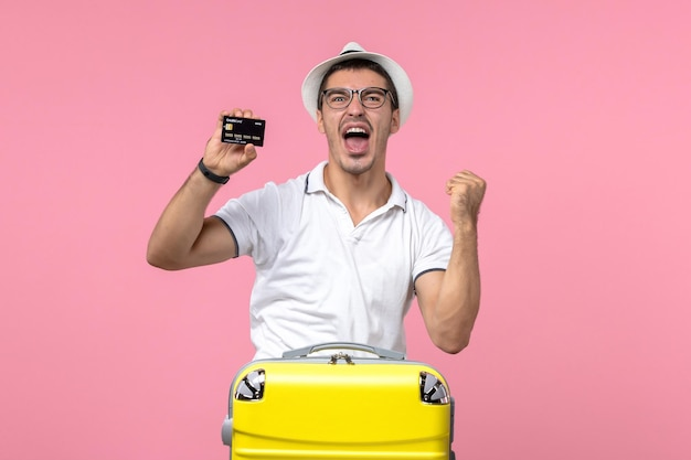 Vooraanzicht van jonge man die emotioneel zwarte bankkaart op lichtroze muur houdt pink
