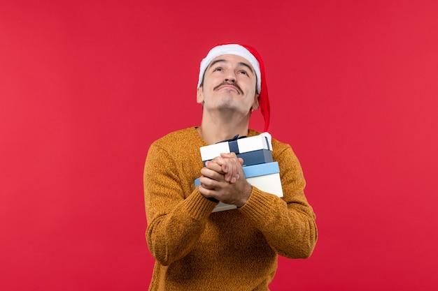 Vooraanzicht van jonge man die huidige dozen houdt die op rode muur bidden