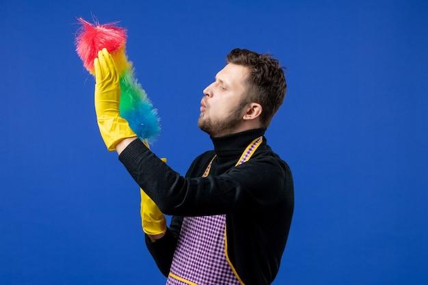 Vooraanzicht van jonge man die op stofdoek op blauwe muur blaast