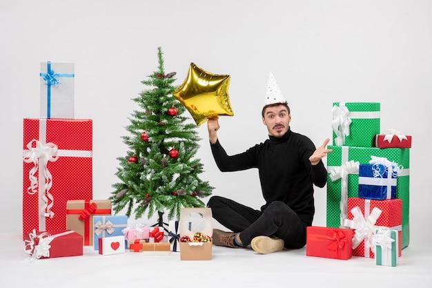 Vooraanzicht van jonge man die rondhangen cadeautjes en gouden stercijfer op witte muur houdt