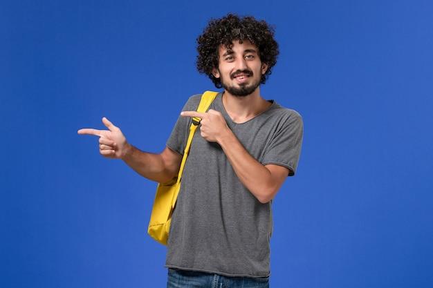 Vooraanzicht van jonge man in grijs t-shirt met gele rugzak, glimlachend op de blauwe muur