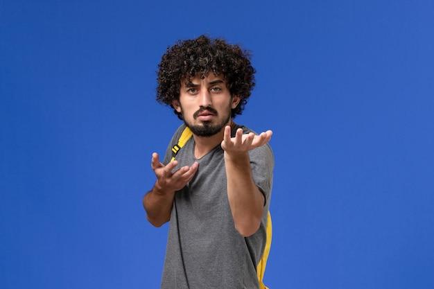 Vooraanzicht van jonge man in grijs t-shirt met gele rugzak poseren met verwarde uitdrukking op blauwe muur