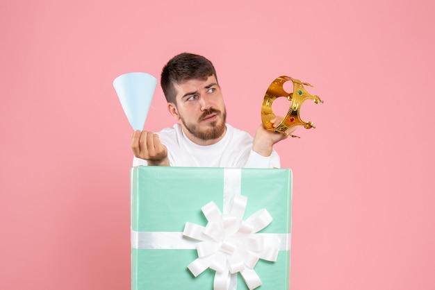 Vooraanzicht van jonge man in huidige doos met kroon op de roze muur