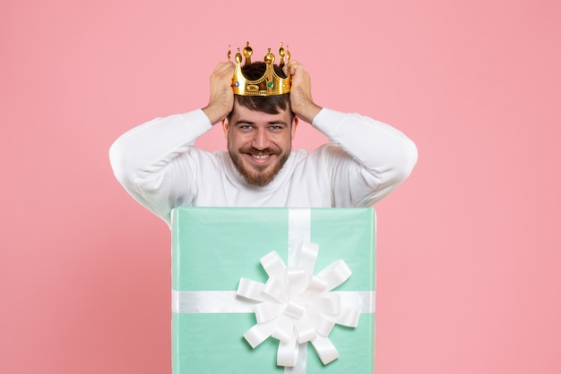 Vooraanzicht van jonge man in huidige doos met kroon op zijn hoofd op de roze muur