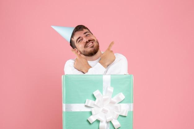 Vooraanzicht van jonge man in huidige doos op de roze muur