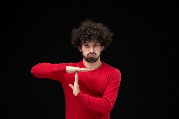 Vooraanzicht van jonge man in rode trui met t-teken op zwarte muur