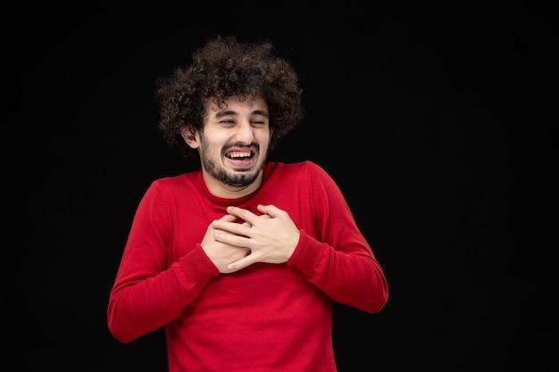 Vooraanzicht van jonge man in rode trui op de zwarte muur