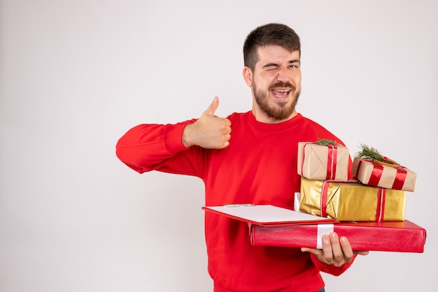 Vooraanzicht van jonge man in rood overhemd met kerstcadeautjes ruzie op witte muur
