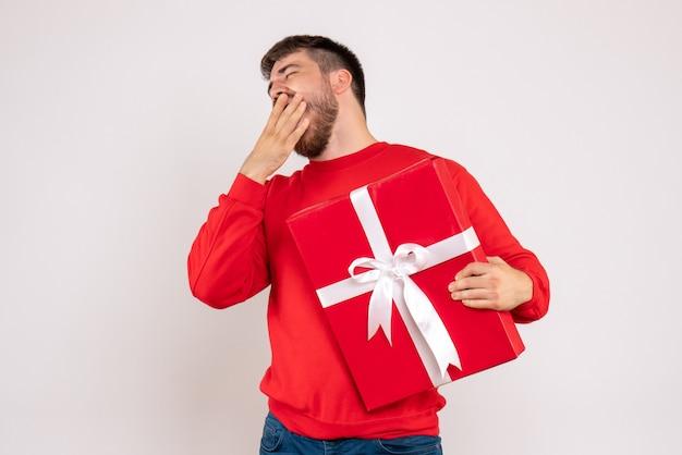 Vooraanzicht van jonge man in rood shirt kerstcadeau te houden en geeuwen op witte muur