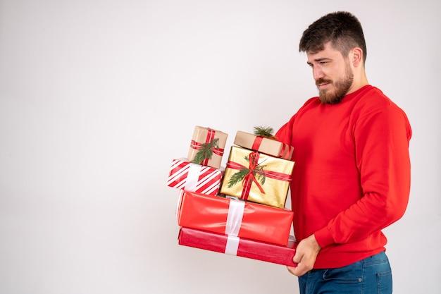 Vooraanzicht van jonge man in rood shirt met kerstcadeautjes op witte muur