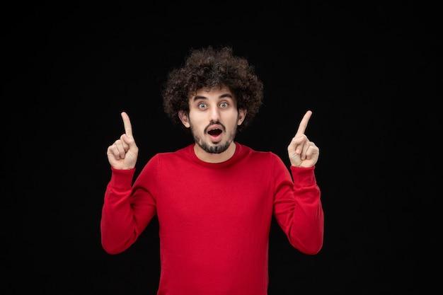 Vooraanzicht van jonge man in rood shirt op zwarte muur