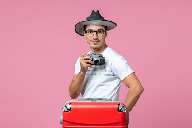 Vooraanzicht van jonge man in zomervakantie die foto's maakt met camera op de roze muur
