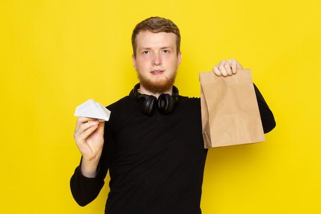Vooraanzicht van jonge man in zwart shirt met papieren vliegtuigje en een goed pakket