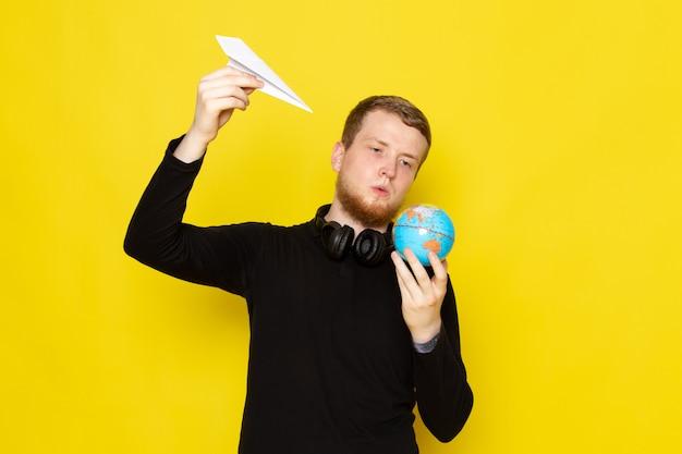 Vooraanzicht van jonge man in zwart shirt met papieren vliegtuigje en kleine globe vorm