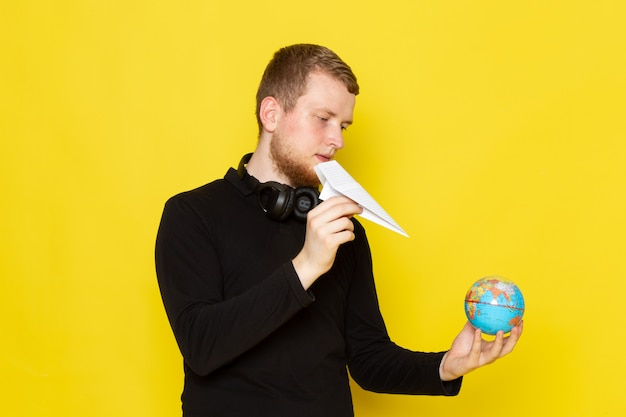 Vooraanzicht van jonge man in zwart shirt met papieren vliegtuigje en kleine wereldbol