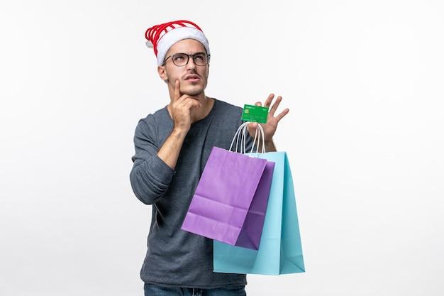 Vooraanzicht van jonge man met bankkaart en pakketten op witte muur