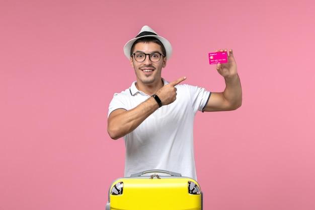 Vooraanzicht van jonge man met bankkaart op vakantie op lichtroze muur