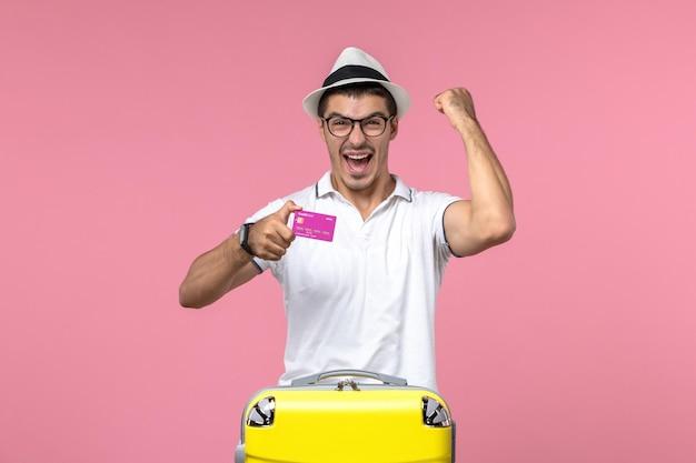 Vooraanzicht van jonge man met bankkaart op zomervakantie op de roze muur pink