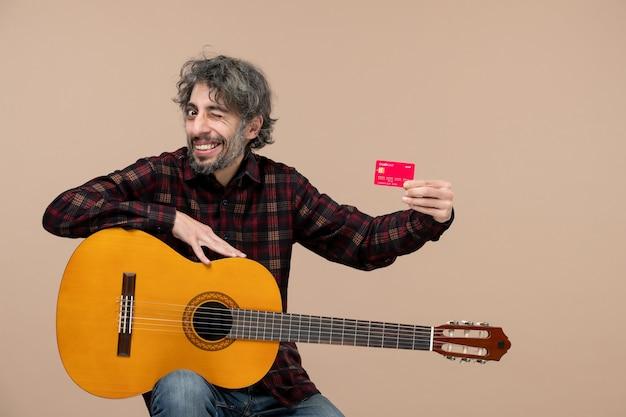 Vooraanzicht van jonge man met gitaar met bankkaart op de roze muur