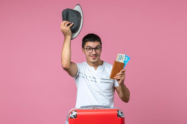 Vooraanzicht van jonge man met hoed en vliegtickets op de roze muur