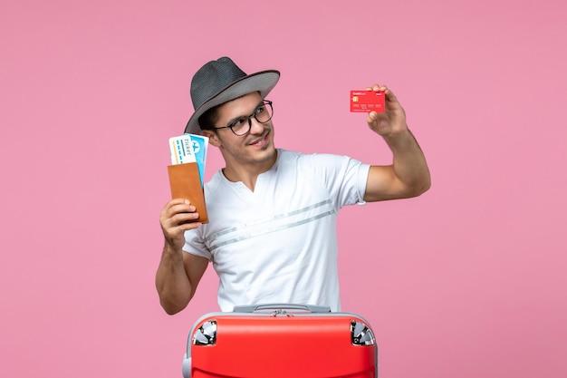 Vooraanzicht van jonge man met kaartjes en bankkaart op de roze muur