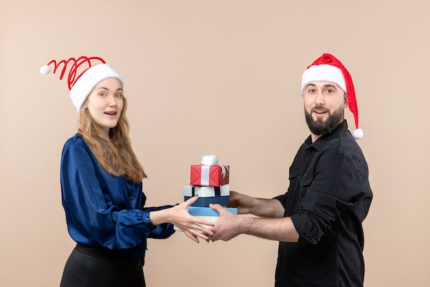Vooraanzicht van jonge man met kerstcadeautjes met vrouw op de roze muur