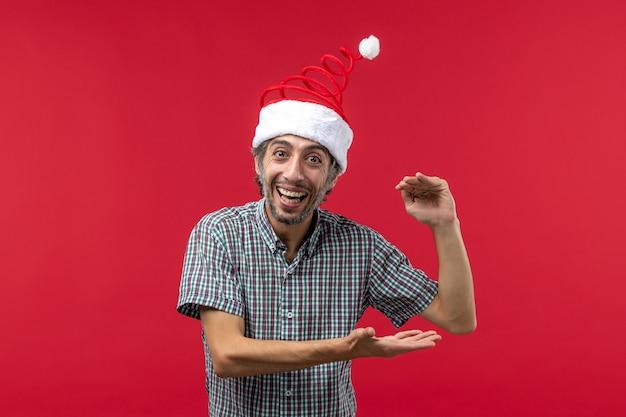 Vooraanzicht van jonge man met opgewonden uitdrukking op de rode muur