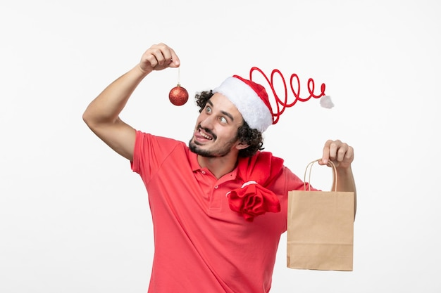 Vooraanzicht van jonge man met pakket met cadeau op witte muur