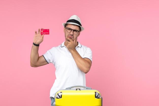 Vooraanzicht van jonge man met rode bankkaart op lichtroze muur light