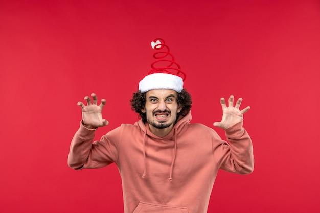 Vooraanzicht van jonge man met schrikkende uitdrukking op rode muur