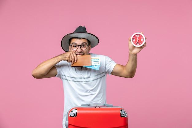 Vooraanzicht van jonge man met vakantiekaartjes en klok op lichtroze muur