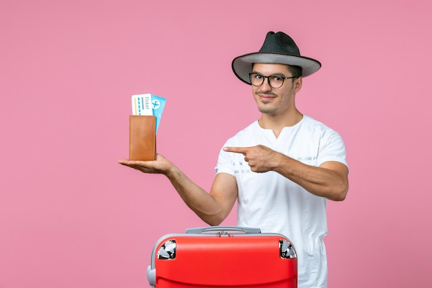 Vooraanzicht van jonge man met vakantiekaartjes in portemonnee op de roze muur