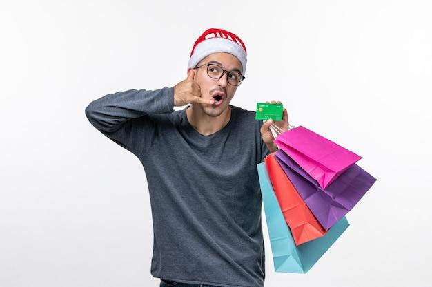 Vooraanzicht van jonge man met vakantiepakketten op witte muur