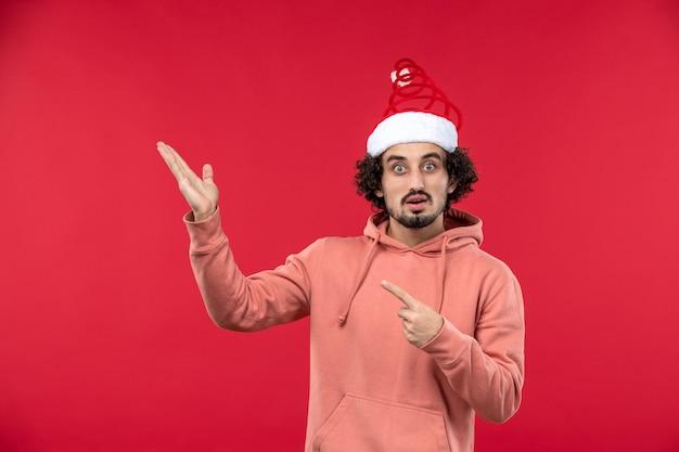 Vooraanzicht van jonge man met verbaasde uitdrukking op rode muur