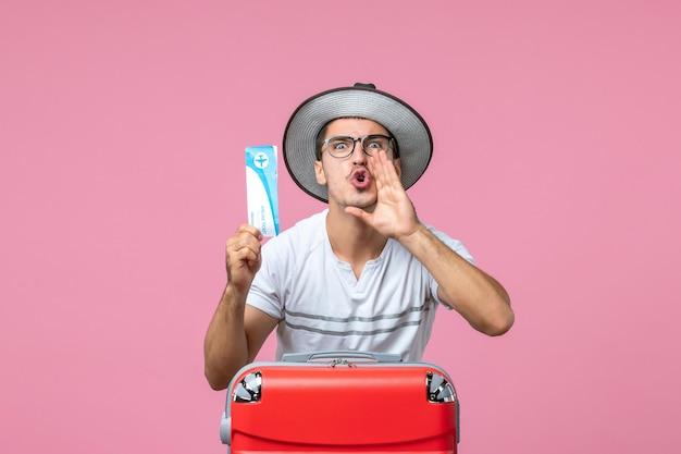 Vooraanzicht van jonge man met vliegticket voor vakantie op de lichtroze muur pink