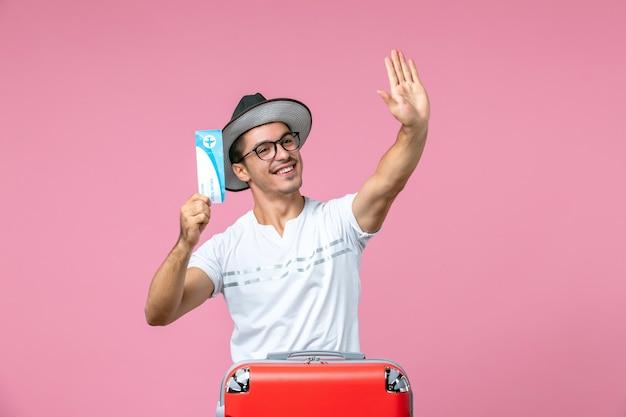 Vooraanzicht van jonge man met vliegticket voor vakantie op de roze muur pink