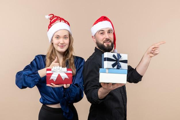 Vooraanzicht van jonge man met vrouw met cadeautjes op roze muur