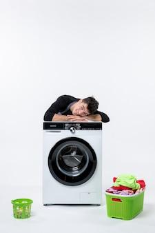 Vooraanzicht van jonge man met wasmachine en vuile kleren op witte muur