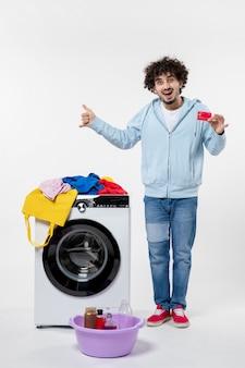 Vooraanzicht van jonge man met wasmachine met bankkaart op witte muur
