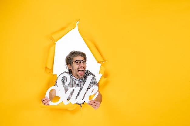 Vooraanzicht van jonge man met witte verkoop schrijven op gele muur