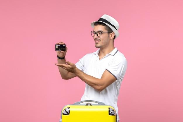 Vooraanzicht van jonge man met zwarte bankkaart op roze muur